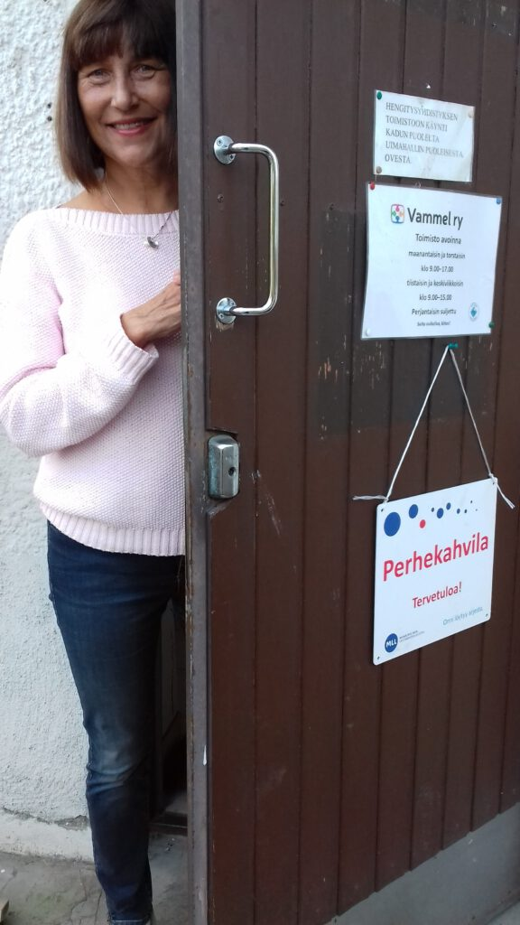 Kuvassa MLL:n paikallisyhdistyksen työntekijä avaamassa ovea perhekahvilaan tulijoille vuonna 2017.