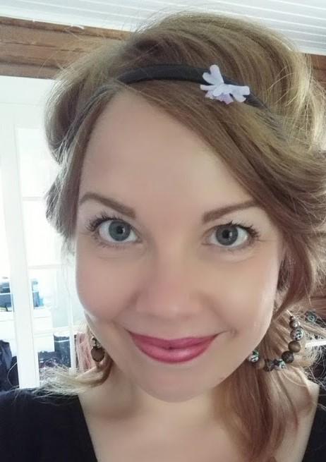 Kuvassa naishenkilö jolla on lila luonnonkukka hiuksissa.